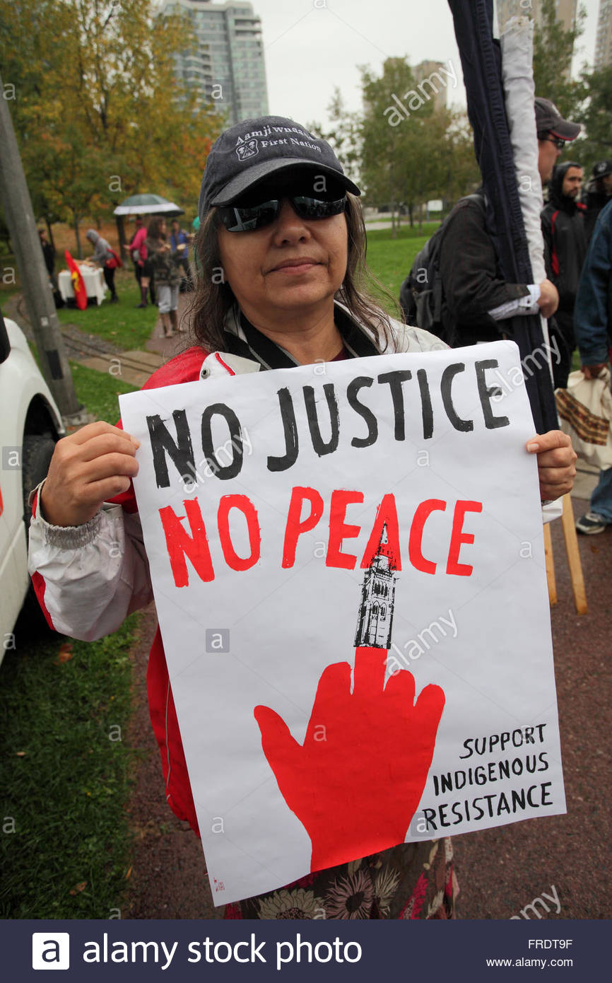 First Nations woman with 'No Justice No Peace ' sign,  No Line 9, anti pipeline Energy East Demonstration,Toronto, - Stock Image