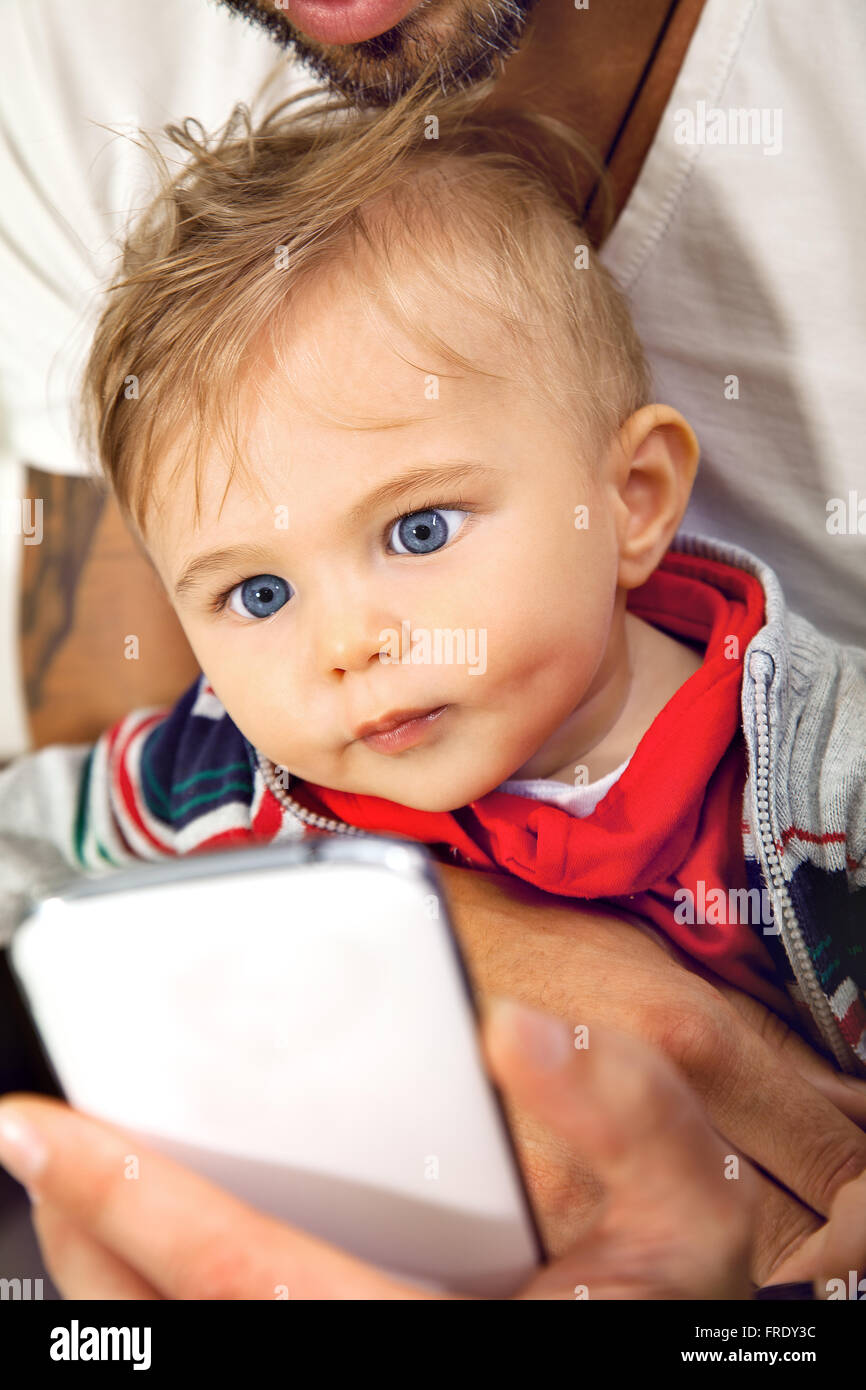 Young cute little boy is watching onto a sellphone with affection embraced by his father. - Stock Image