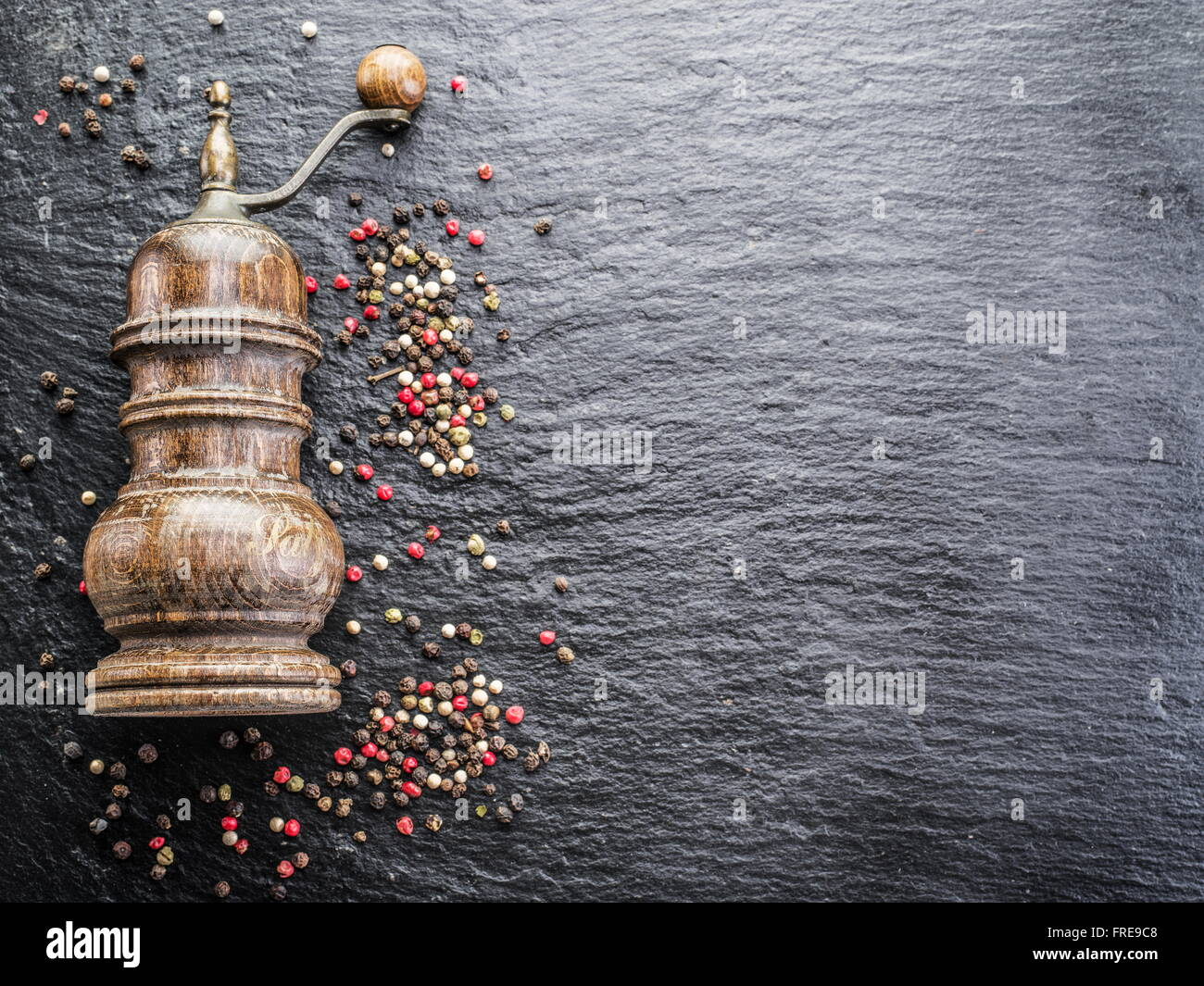 Colorful peppercorns and old pepper mill on the black background. - Stock Image