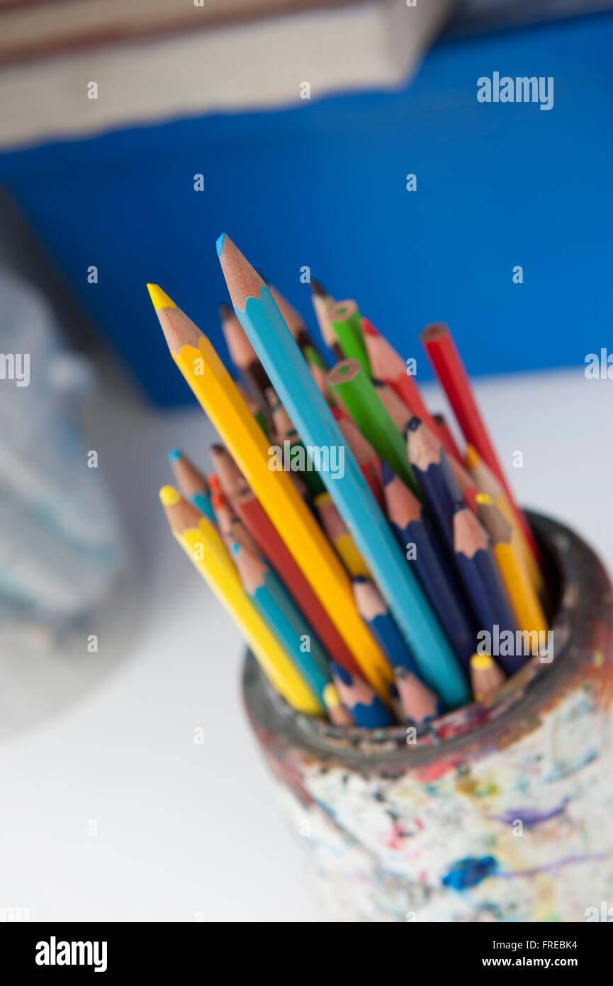 Coloured pencils in a paint-stained pot - Stock Image