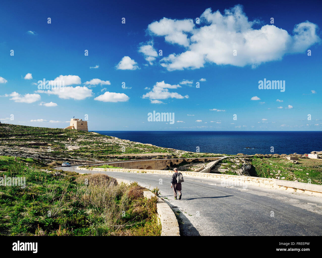shepherd on road near fort and mediterranean coast view of gozo island in malta - Stock Image