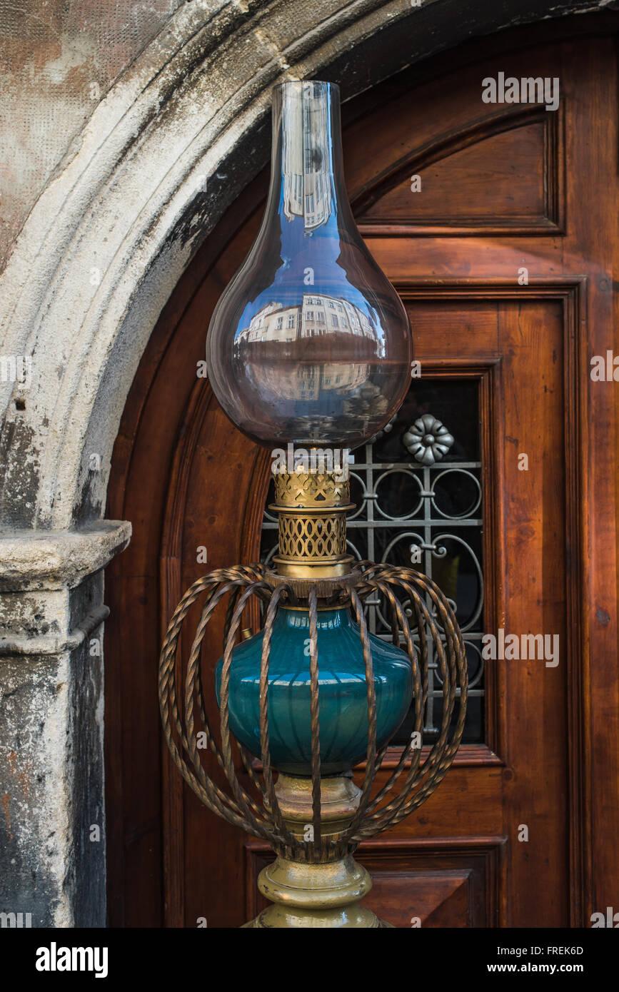 Vintage kerosene lamp isolated. Old austran doors on background - Stock Image