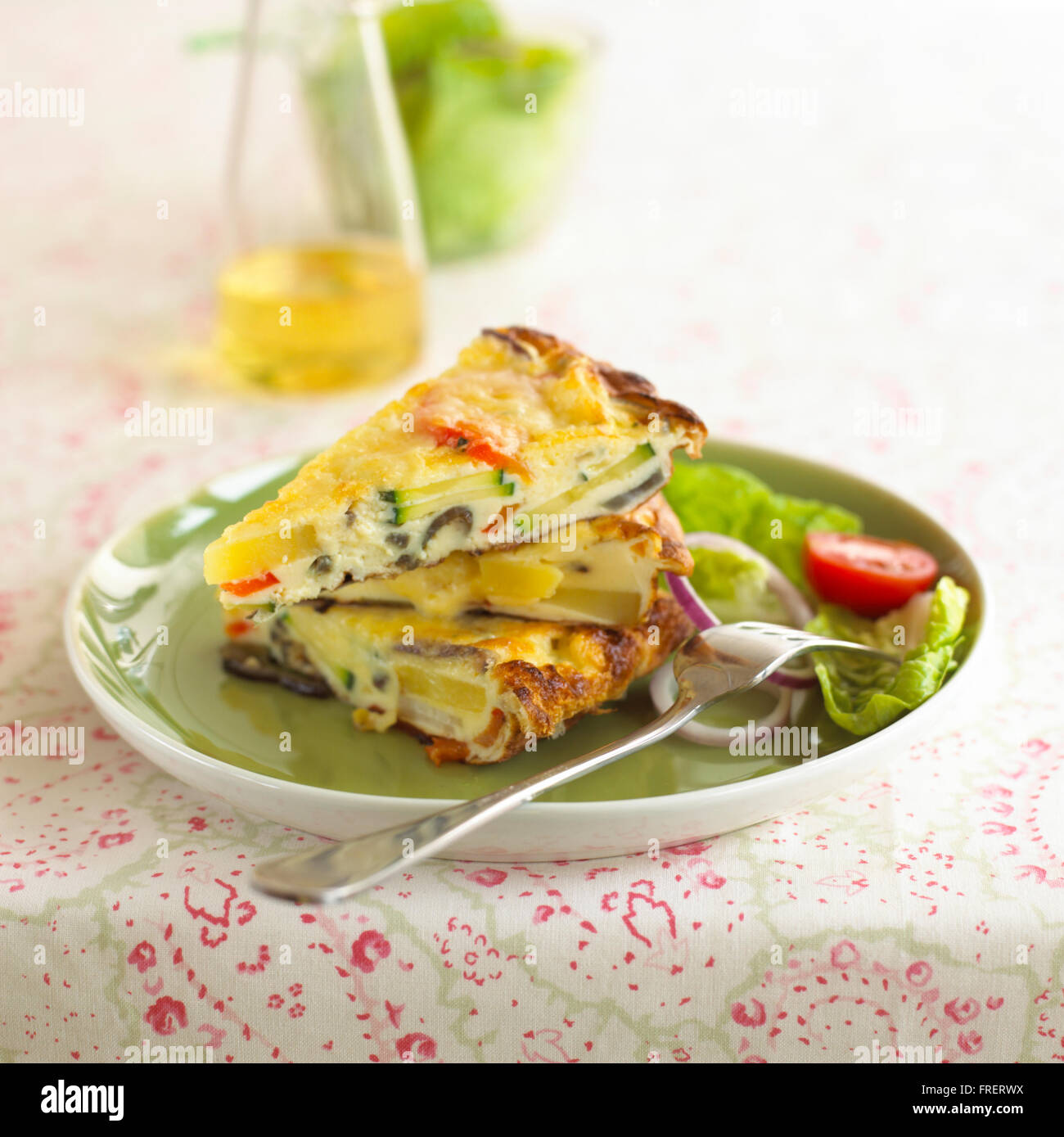 Frittata provencale, three wedges of omelette containing vegetables on plate with side salad and fork - Stock Image