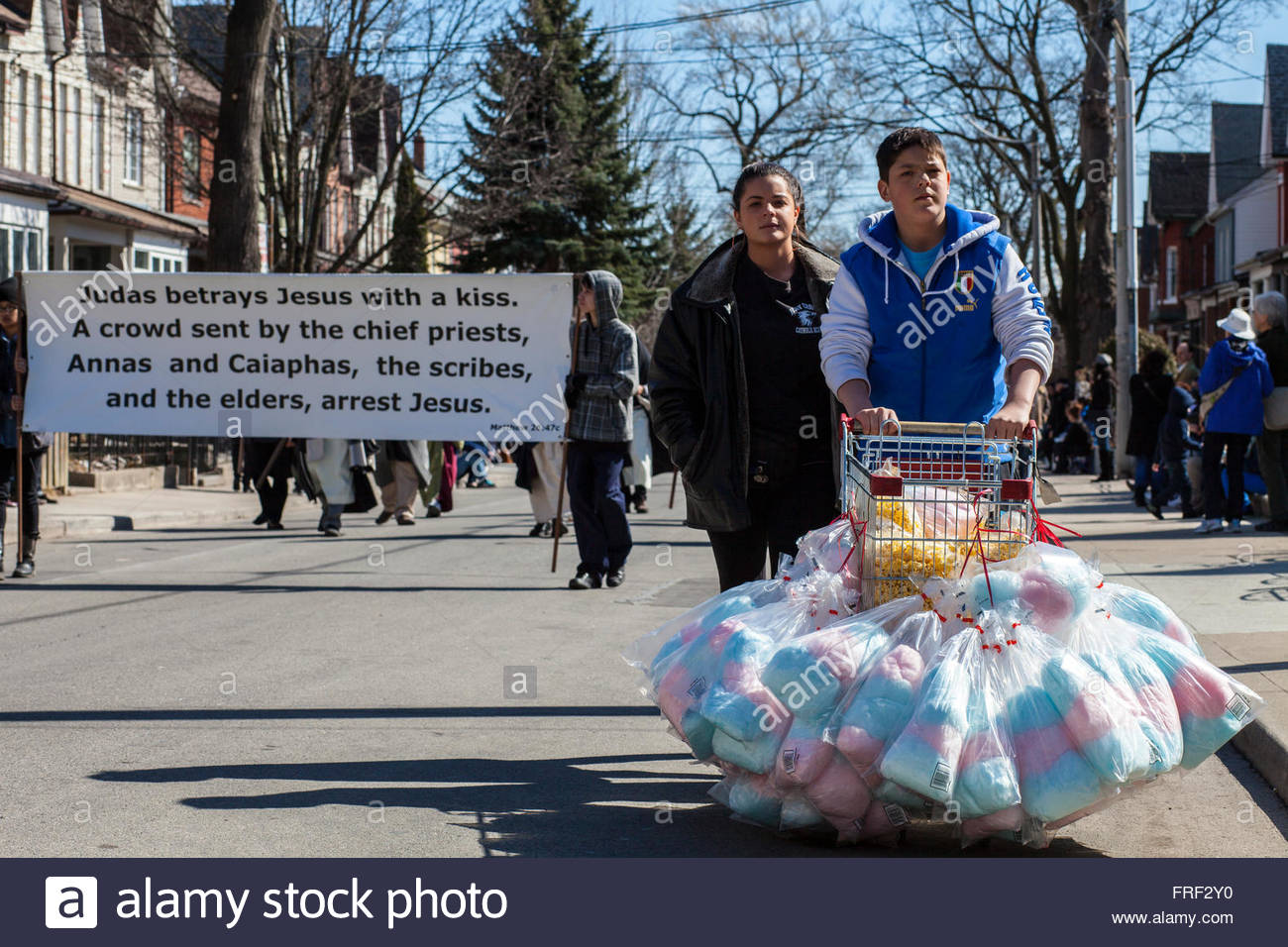 Judas betrays Jesus who is arrested sign, 2 kids selling candy floss, Easter, Stations of the Cross, Good Friday - Stock Image