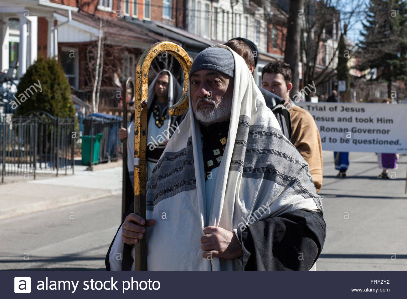 Old Shepherd man with ornate staff, Trial of Jesus sign behind, Good Friday parade Easter, Stations of the Cross, - Stock Image