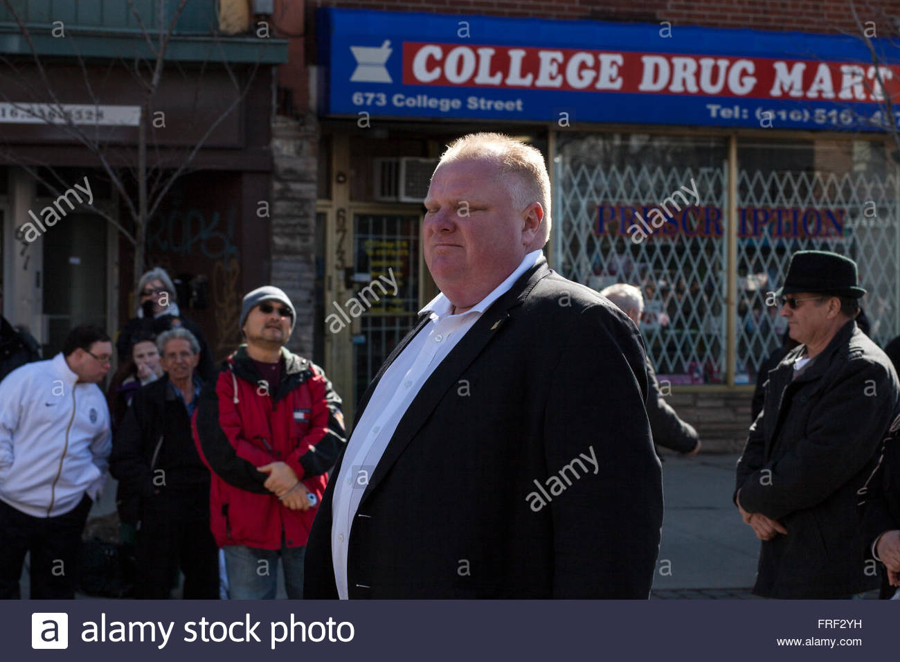 Mayor Rob Ford closes his eyes as he walks past staring spectators and College Drug Mart, Easter, Stations of the - Stock Image