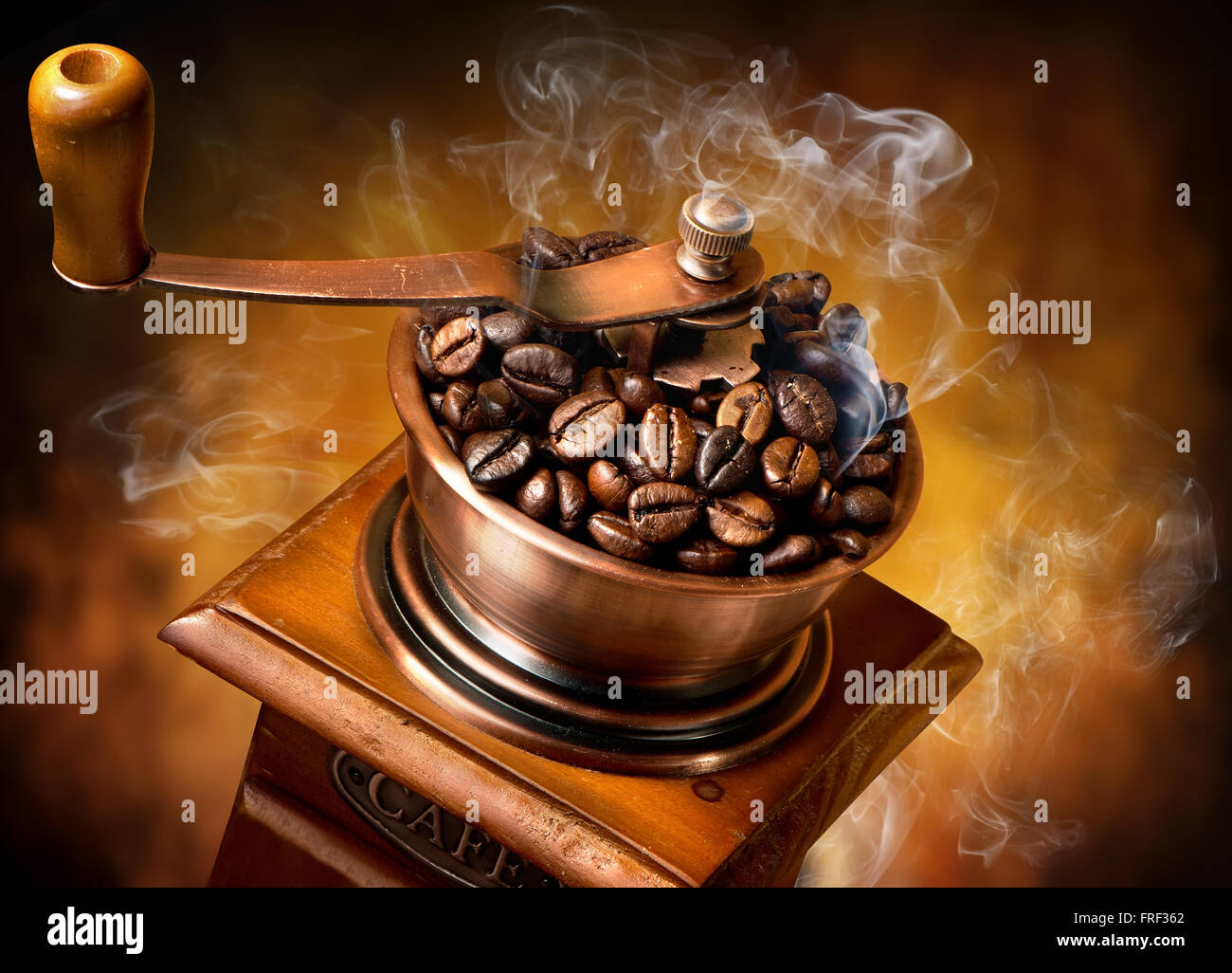 Old wooden coffee-mill on an orange background - Stock Image