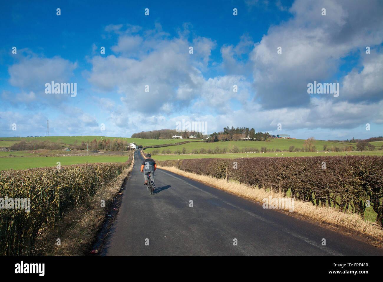 A cyclist cycling towards Thortonhall, South Lanarkshire - Stock Image