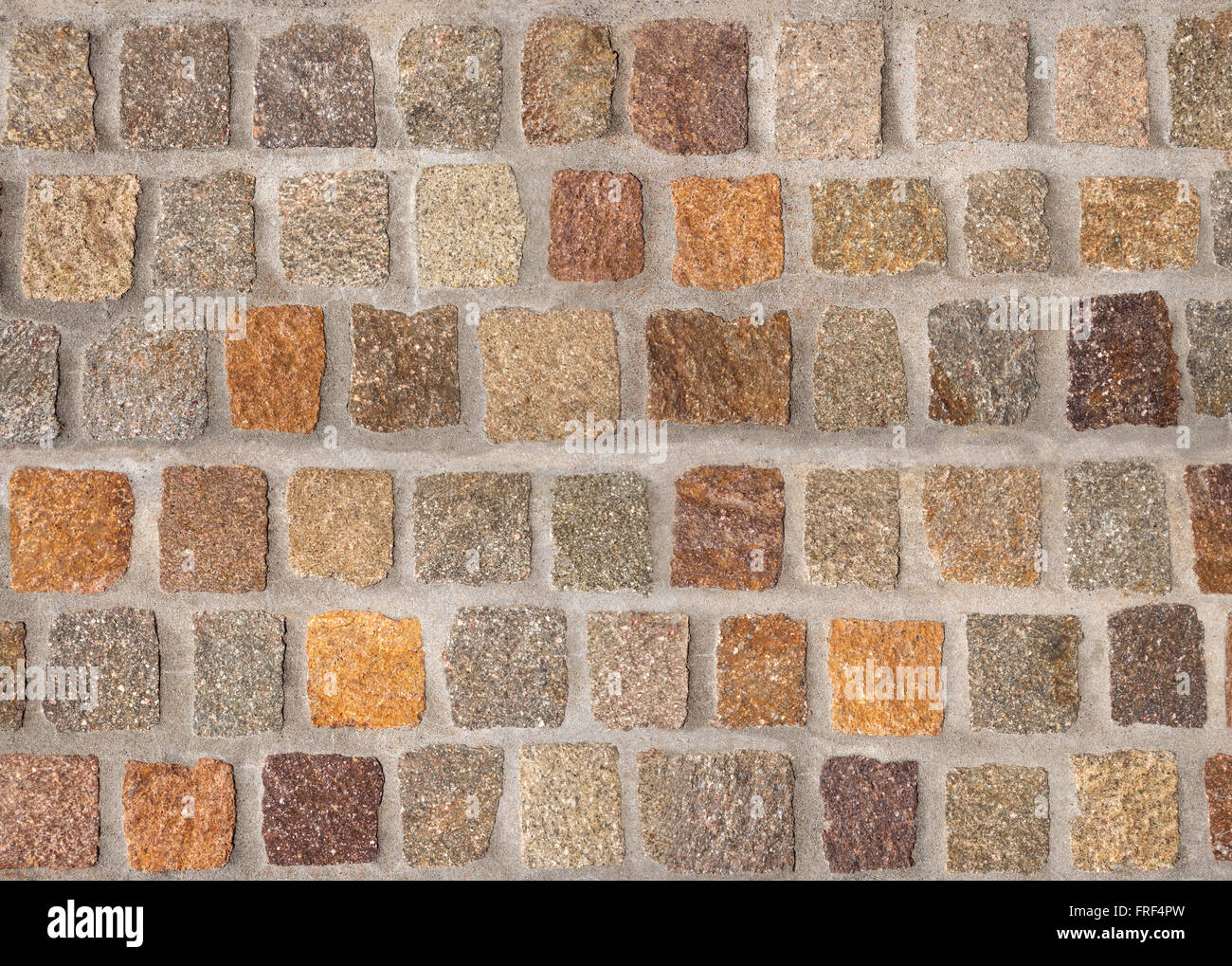 Pattern of varicolored cobblestones in brown and gray in close-up - Stock Image