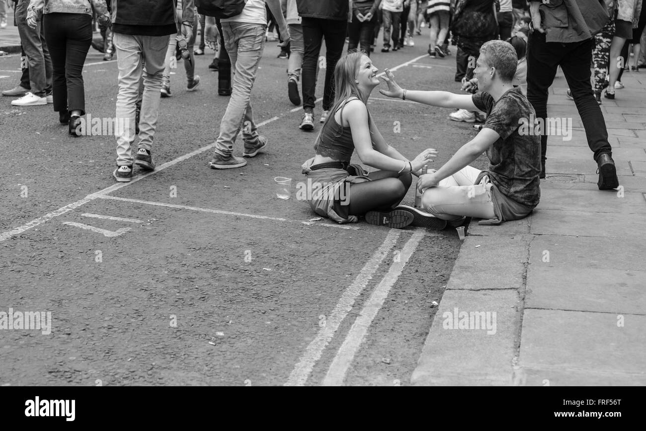 Young couple sitting and drinking in the middle of the road during Notting Hill Carnival street parade. - Stock Image