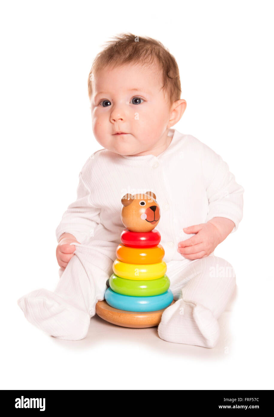 baby with wooden stacking toy white background - Stock Image