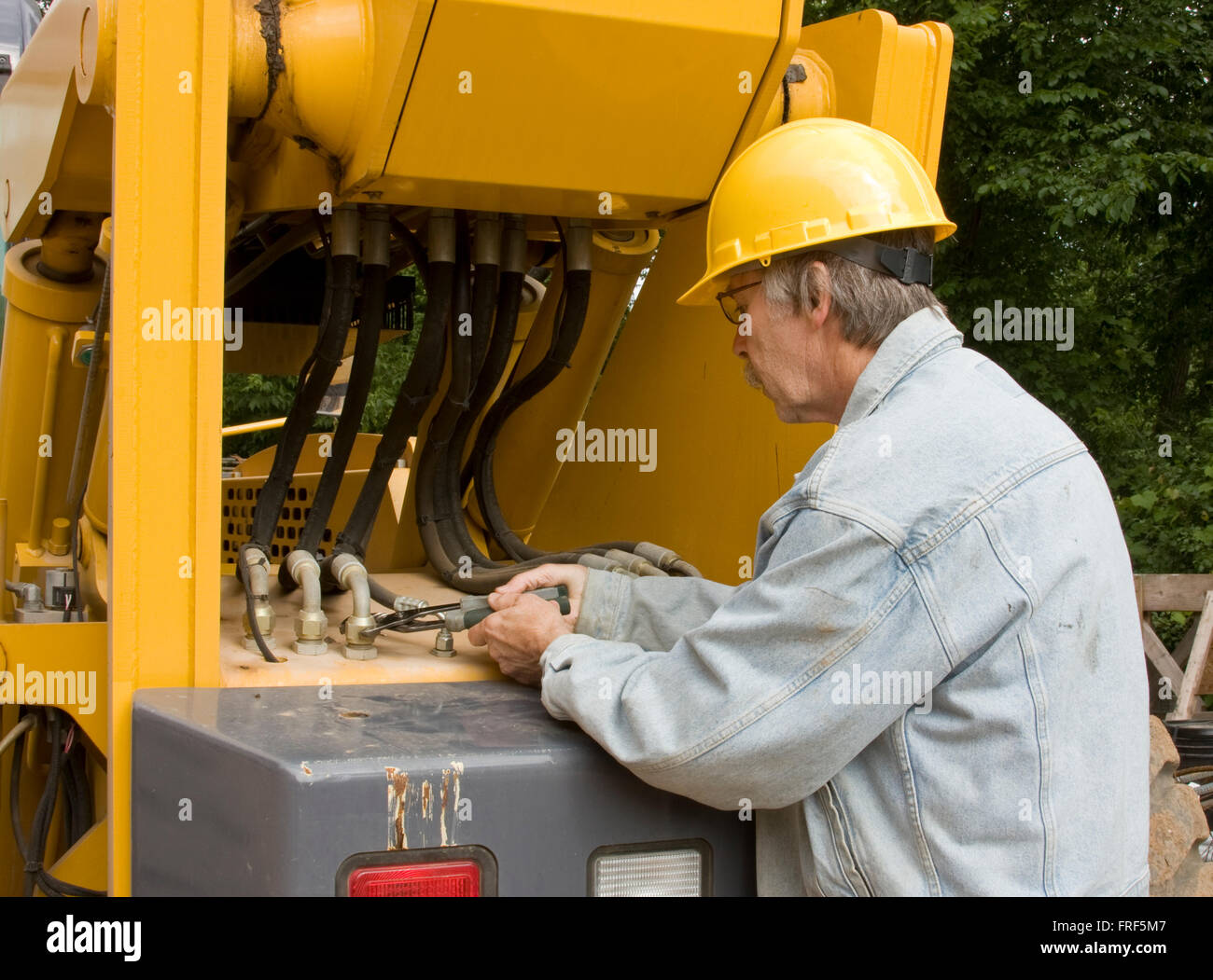 heavy equipment mechanic repairing hydraulic hoses - Stock Image