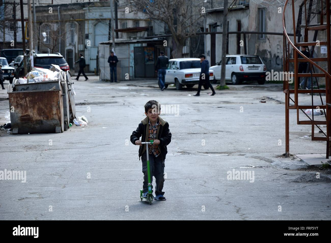 BAKU, AZERBAIJAN - MARCH 19 2014 Young boy on a scooter in Sovietskaya, a poor and unmodernised part of Baku, capital - Stock Image
