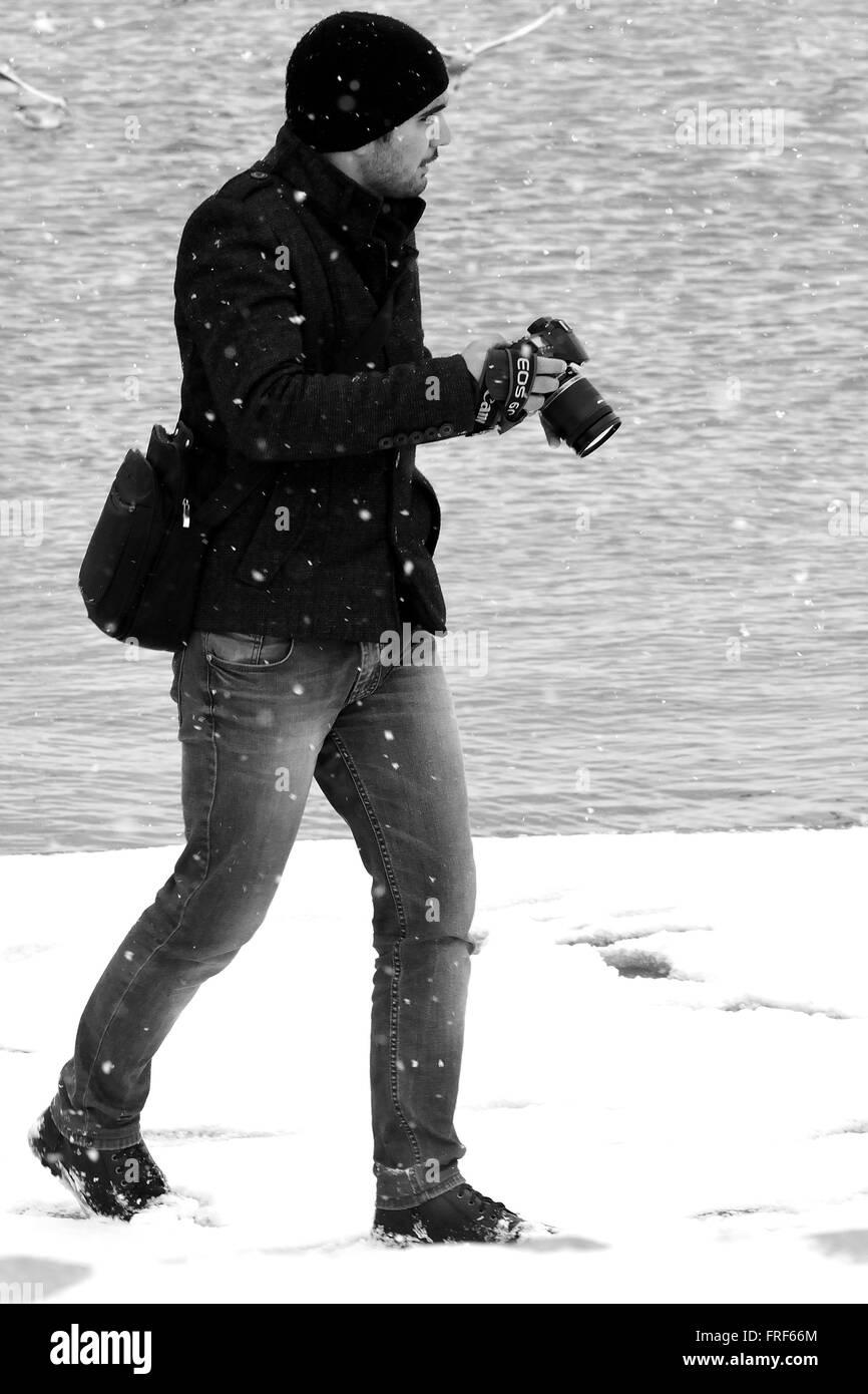 BAKU, AZERBAIJAN - JANUARY 31 2104 Photographer on Baku Bulvar in the snow, in the capital of Azerbaijan, in black - Stock Image