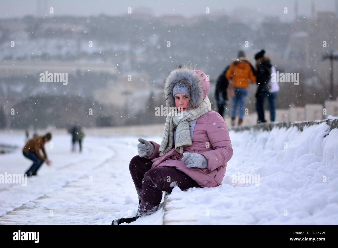 Young girl in a pink coat well wrapped-up on Baku Bulvar in the snow, in the capital of Azerbaijan. - Stock Image