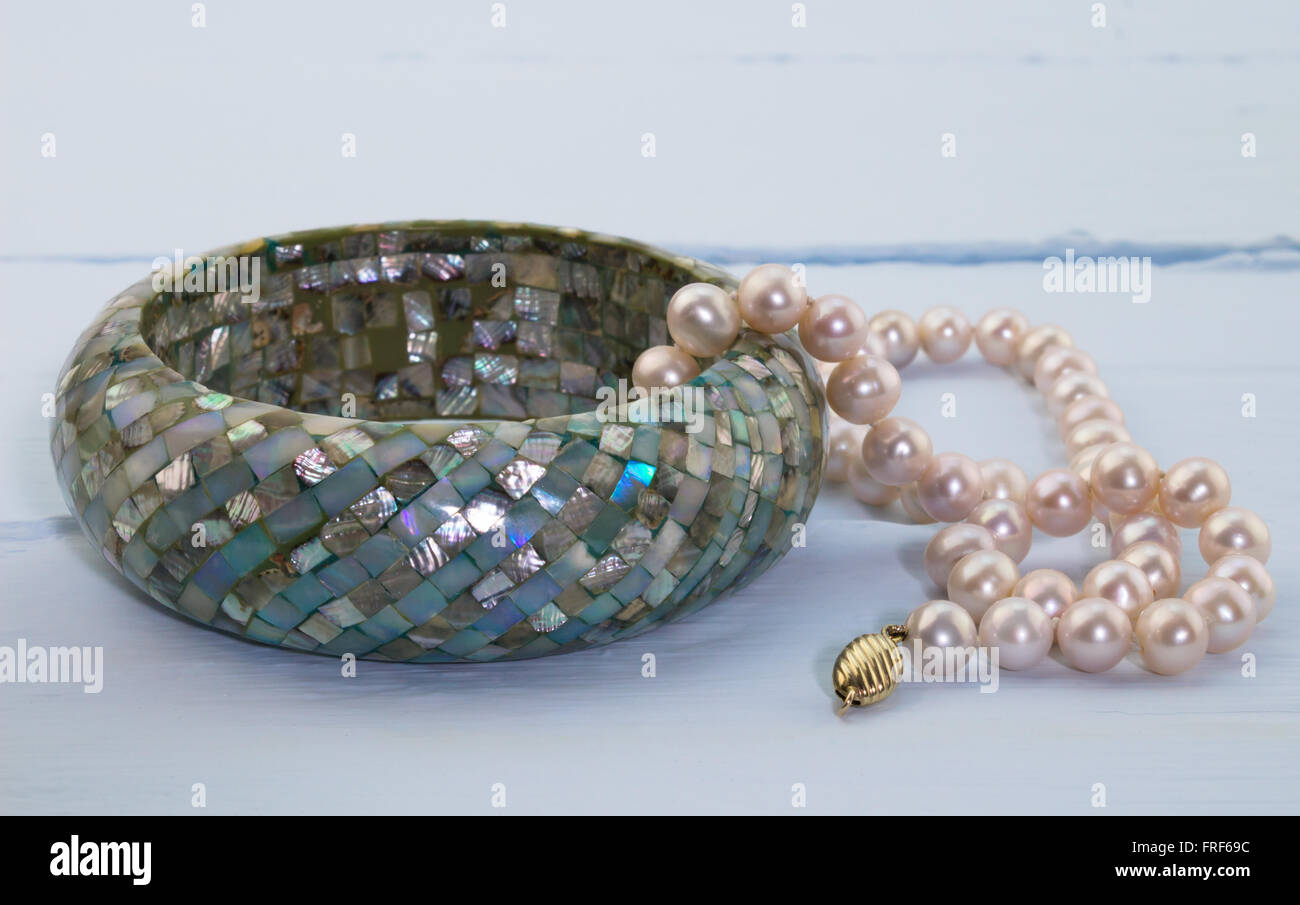 Photo of blue painted wood background with pink pearl necklace and mozaic blue mother of pearl bangle - Stock Image