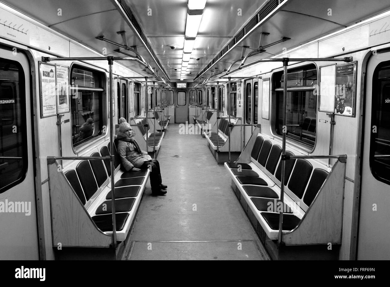 Girl in an empty carriage on the Baku Metro. A child sits alone on a subway train in the capital of Azerbaijan - Stock Image