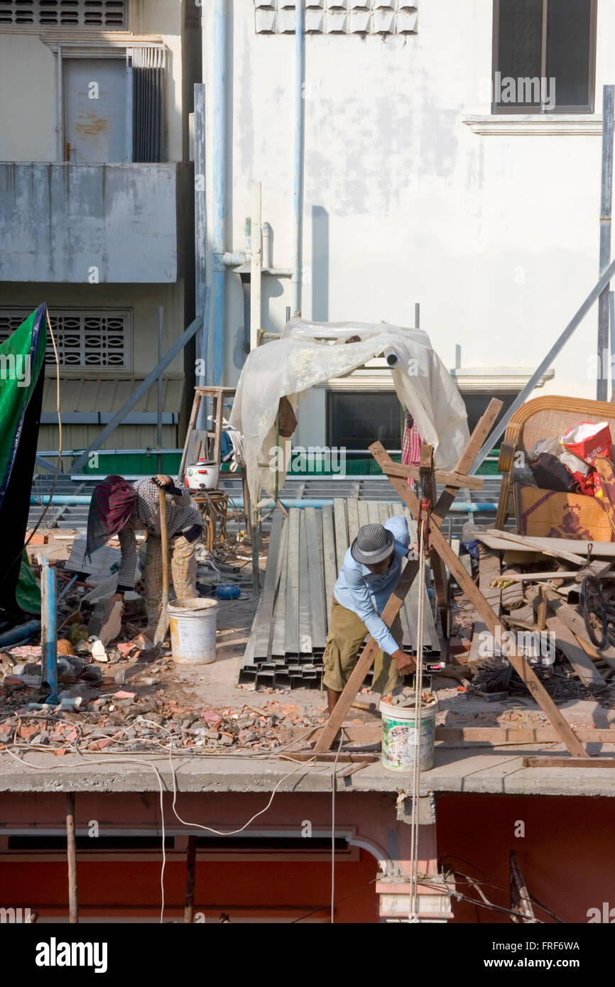 Construction workers are working on a building renovation at a construction site in Phnom Penh, Cambodia. - Stock Image