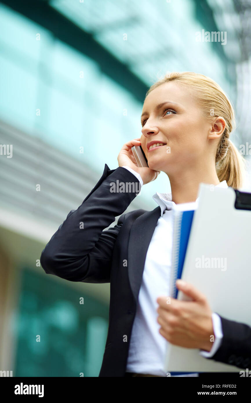 Modern businesswoman speaking on the cellular phone outside - Stock Image