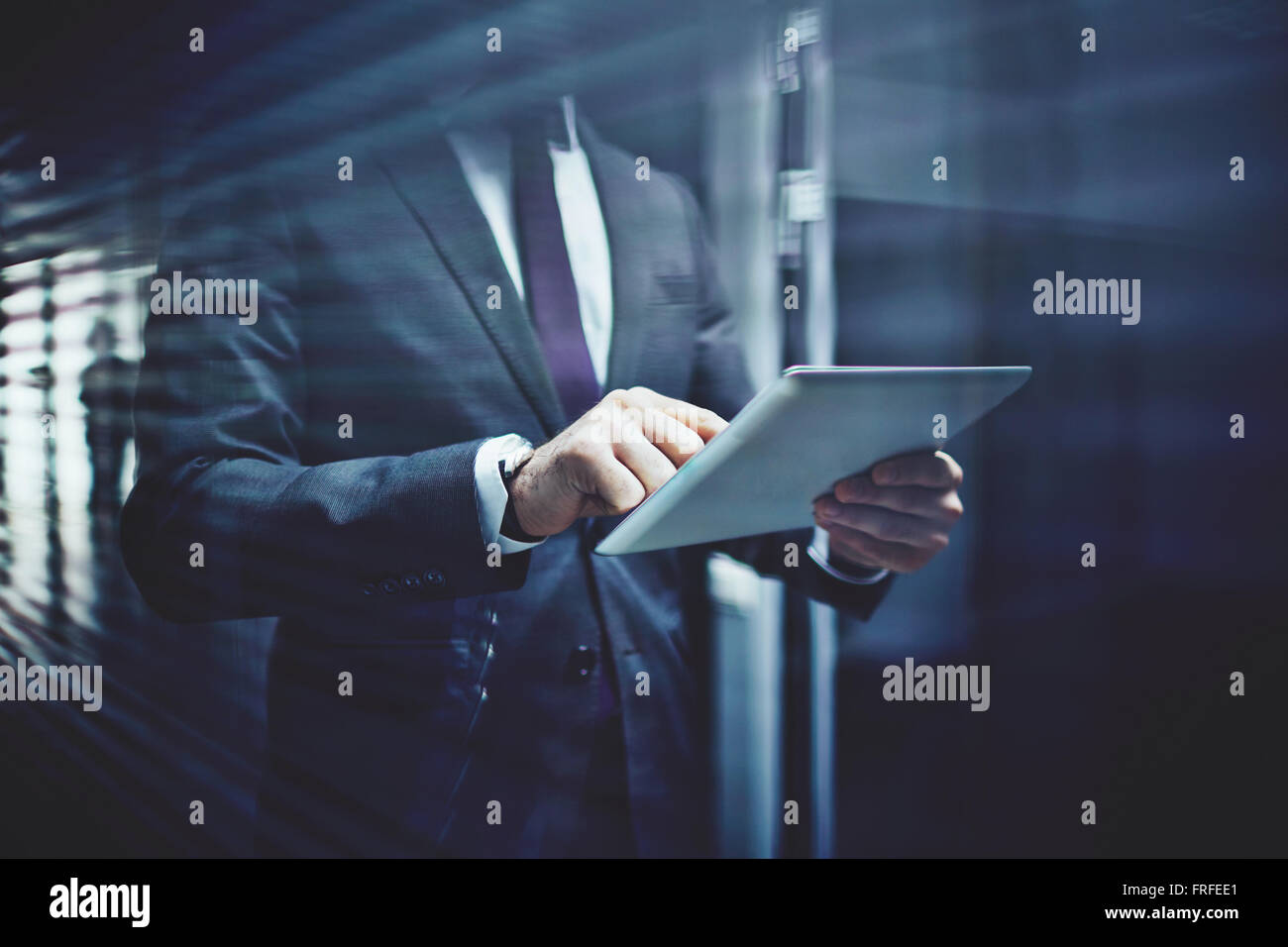 Close-up of businessman with touchpad networking in corridor of office building - Stock Image