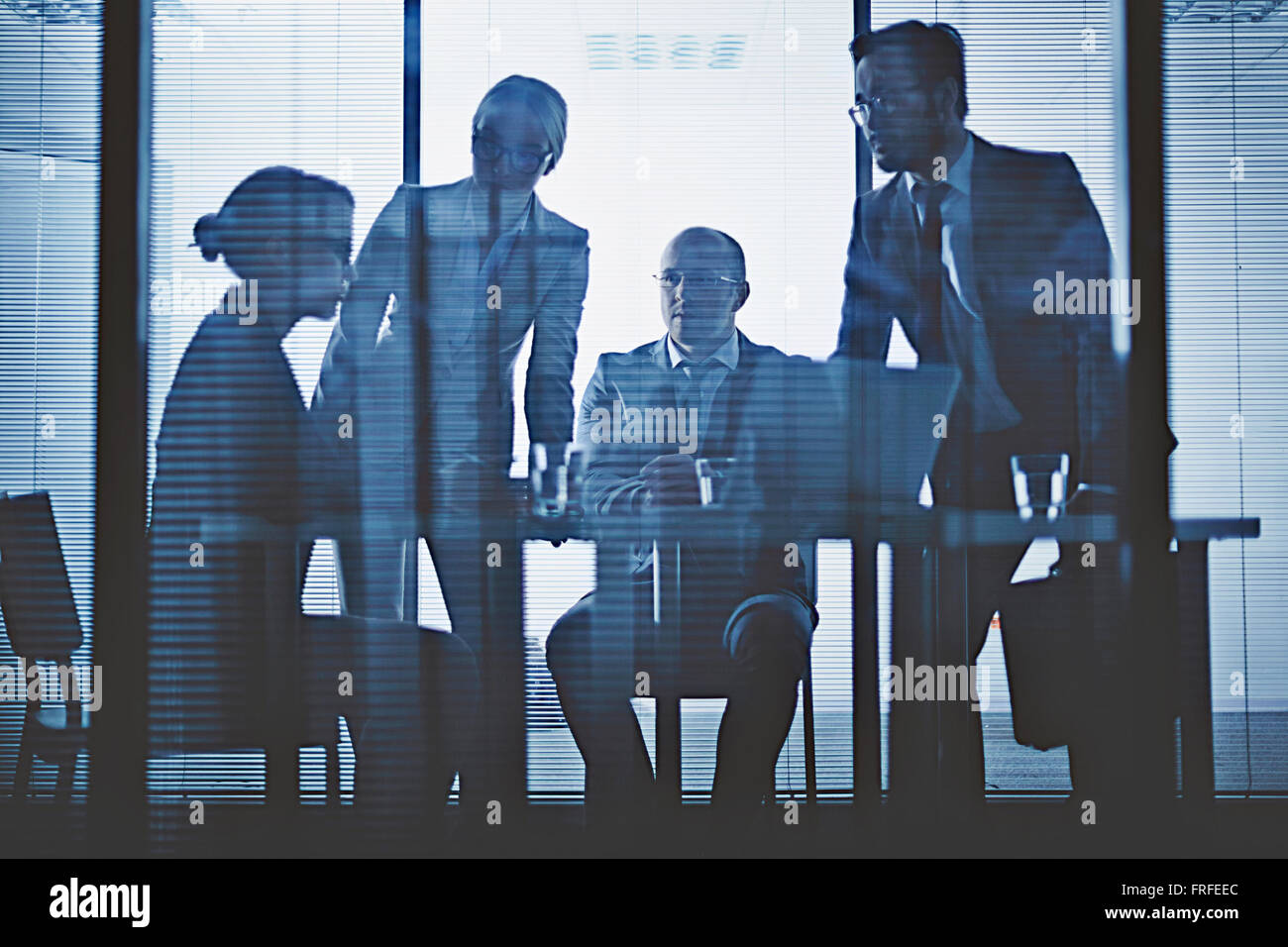 Young co-workers communicating at meeting in office - Stock Image