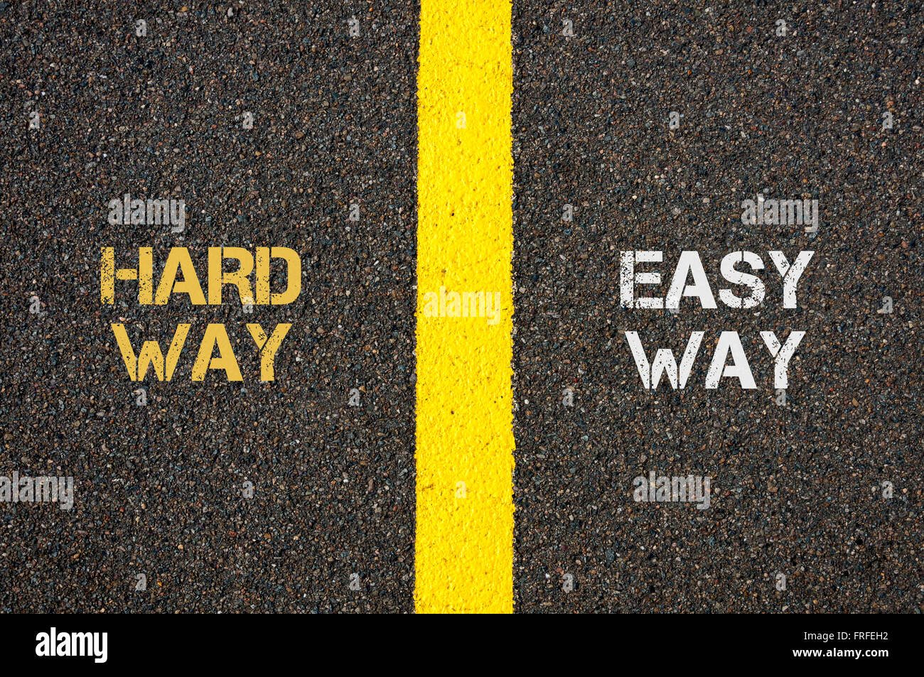 Antonym concept of HARD WAY versus EASY WAY written over tarmac, road marking yellow paint separating line between - Stock Image