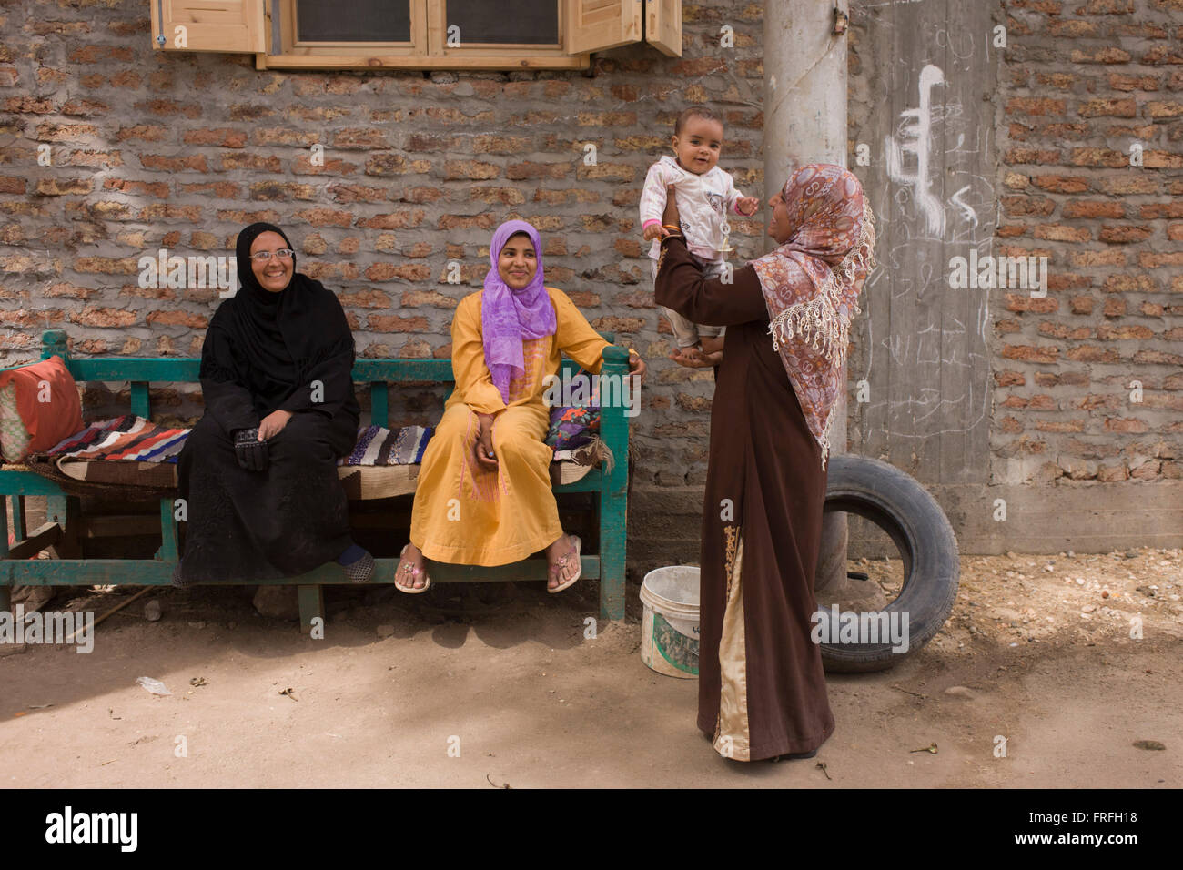 A local family enjoy their youngest child in Bairat, a village on the West Bank of Luxor, Nile Valley, Egypt. The - Stock Image