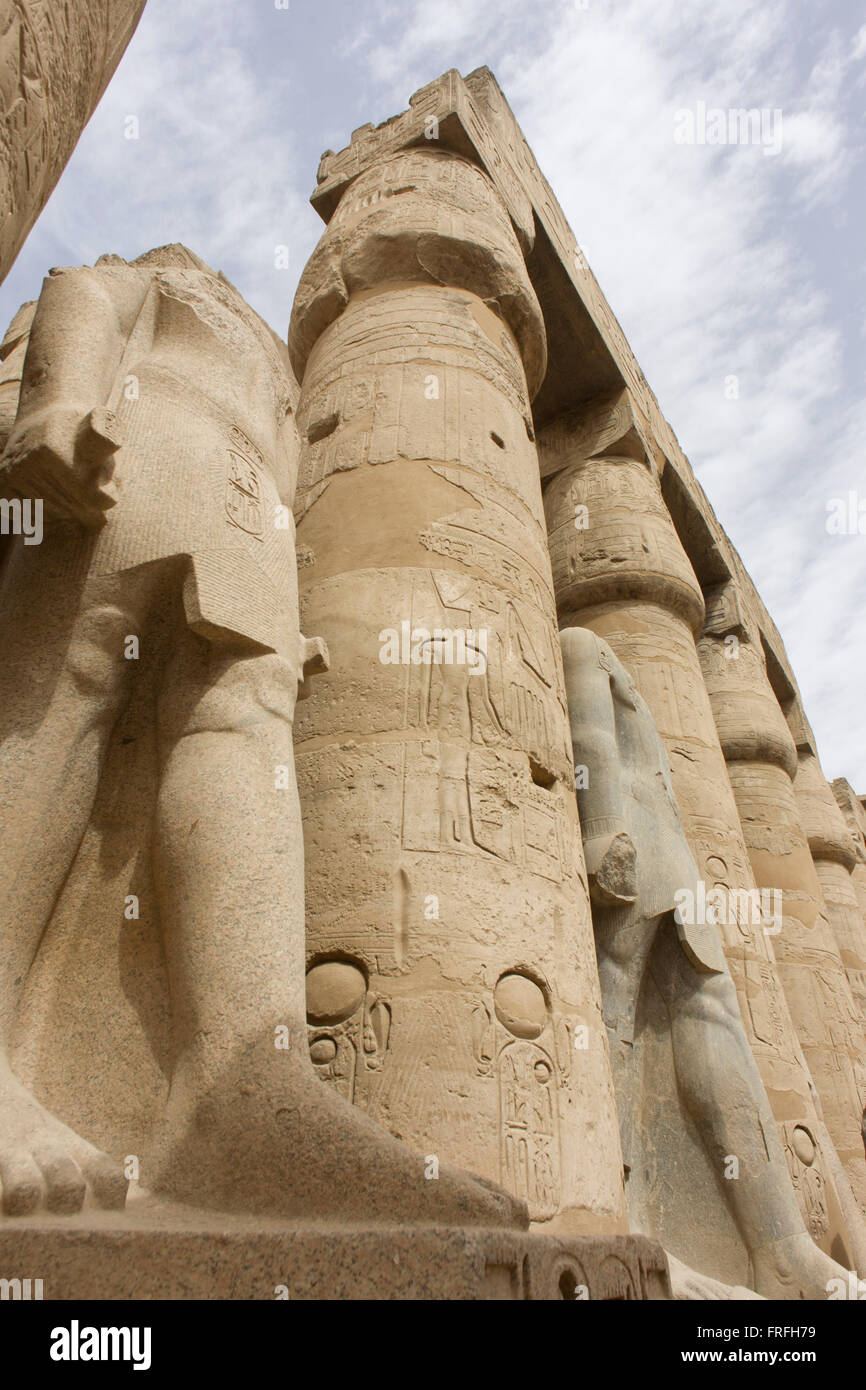 Tall Colossi in the Court of Ramesses II at the ancient Egyptian Luxor Temple, Nile Valley, Egypt. The temple was - Stock Image