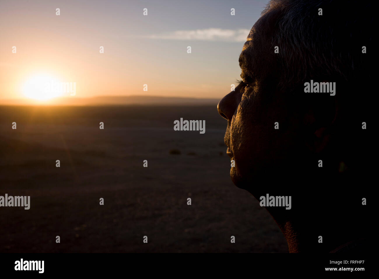 A local Egyptian businessman looks thoughtfully into a setting sun while on sand dunes of a desert enviroment, near - Stock Image
