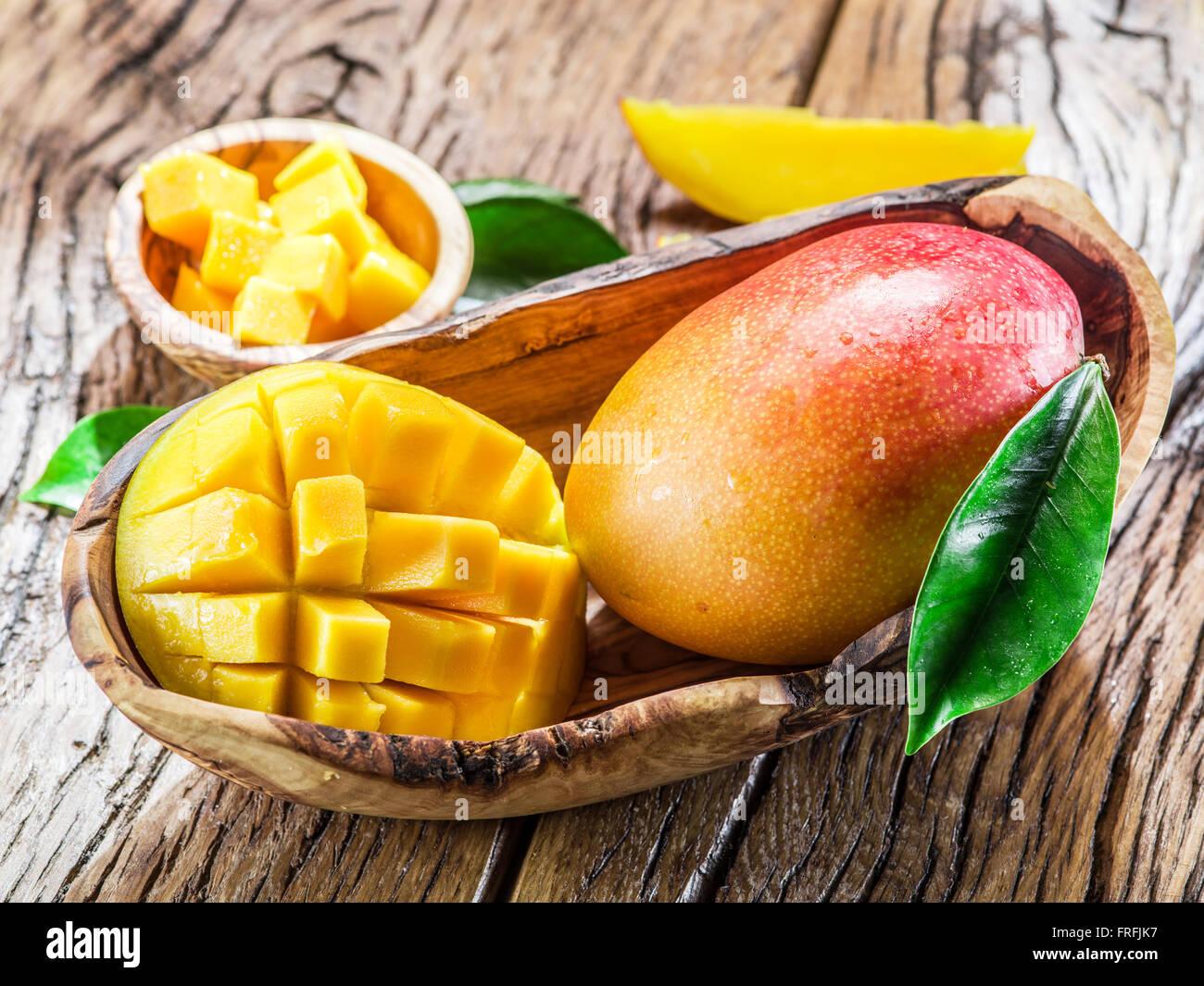 Mango fruit and mango cubes on the wooden table. - Stock Image