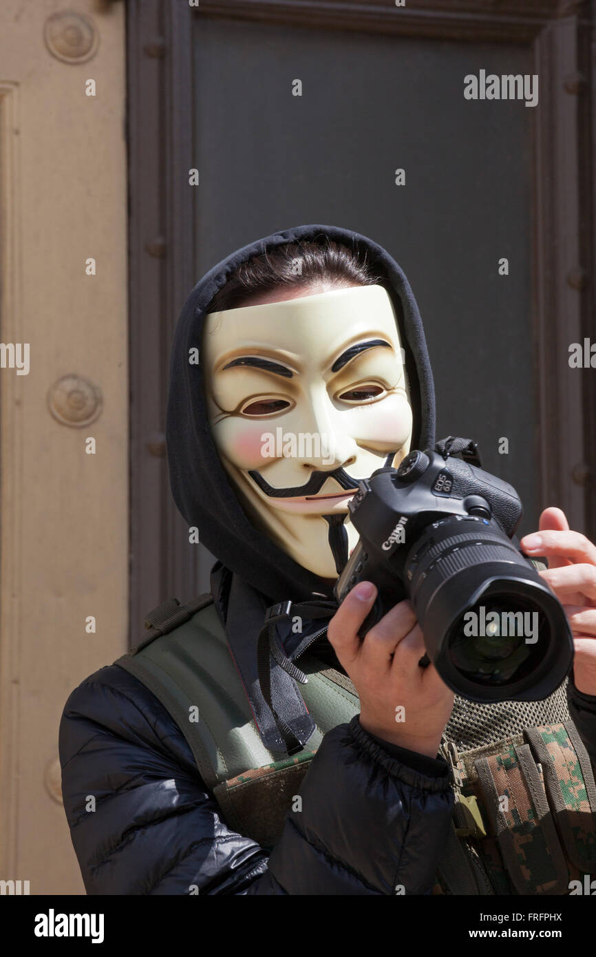 Detroit, Michigan - A man wearing a Guy Fawkes mask takes pictures during the Marche du Nain Rouge. - Stock Image