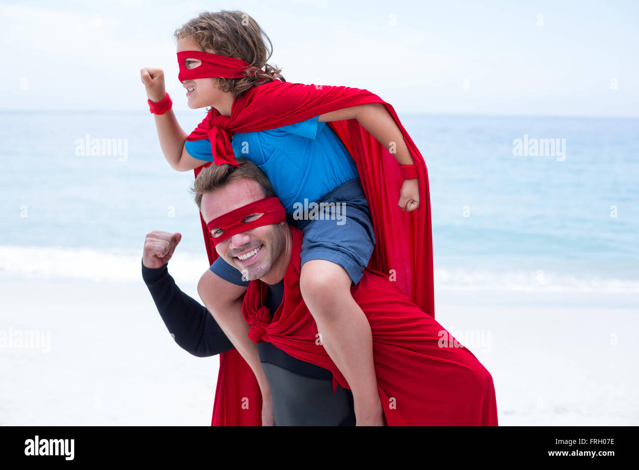Father and son in superhero costume pretending to run Stock Photo