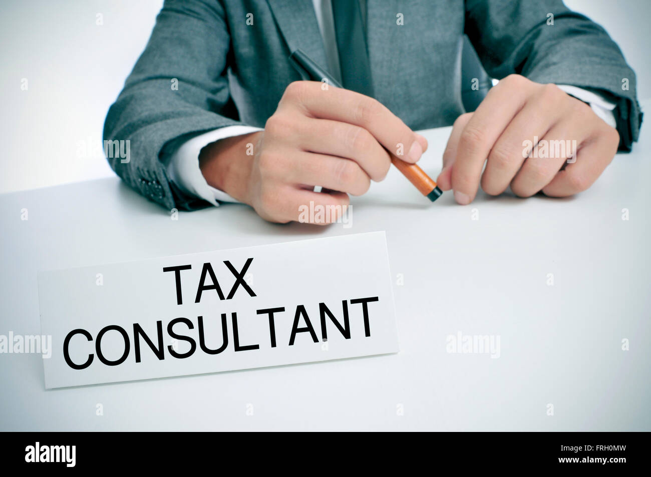 a man wearing a gray suit sitting at his office desk with a signboard in front of him with the text tax consultant - Stock Image