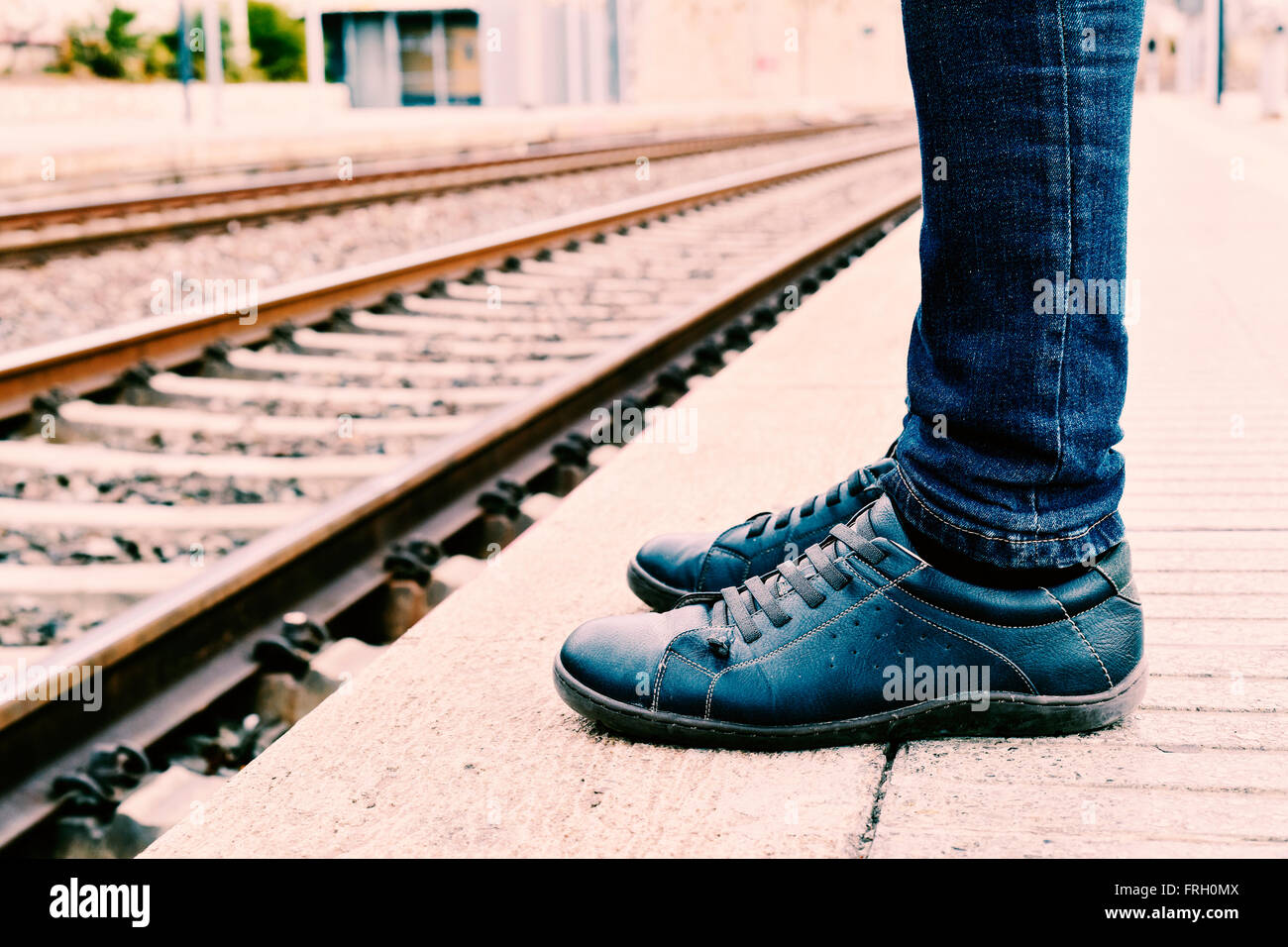 closeup of the feet of a young man wearing jeans who is waiting for the train at the platform of the train station - Stock Image