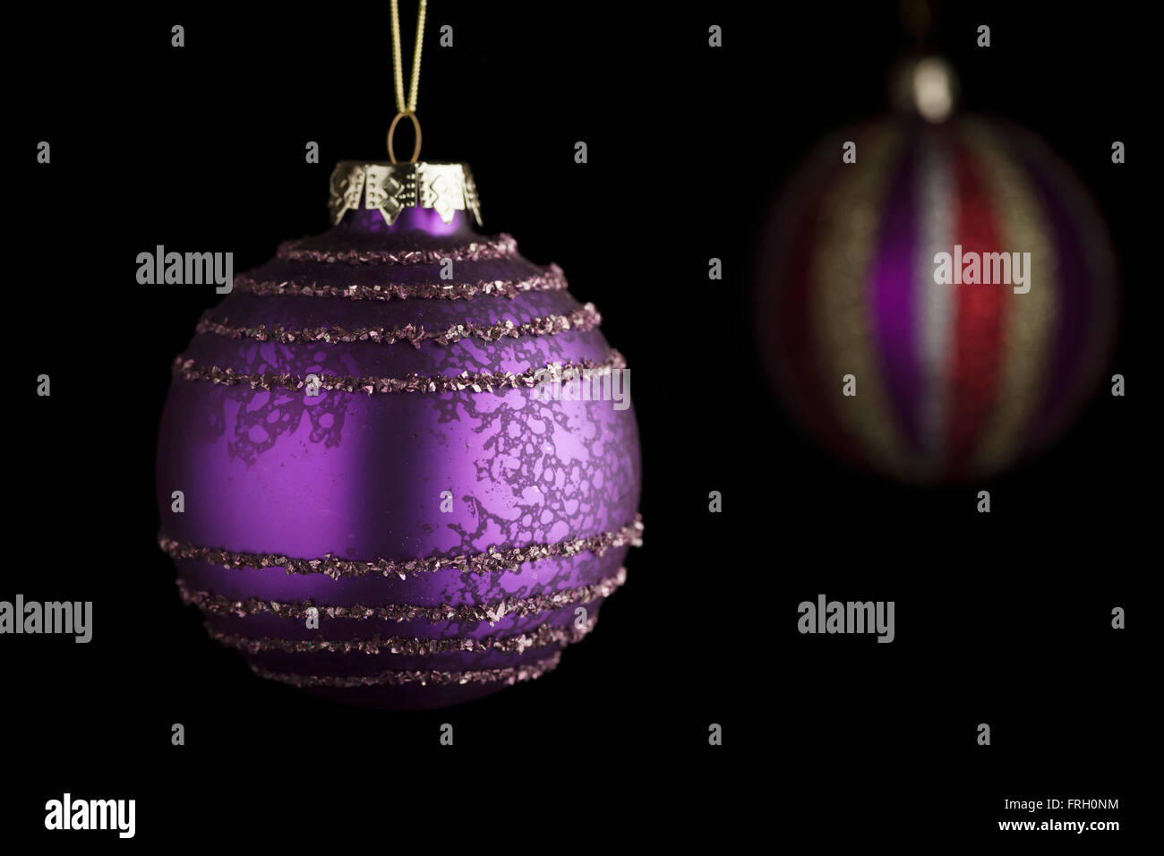 Purple Christmas ball in the foreground with vertically striped Christmas ball in the blurred background in the - Stock Image