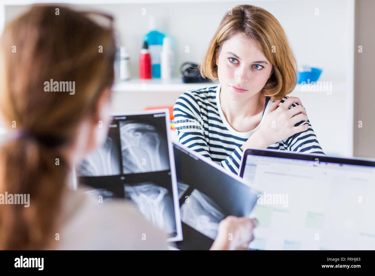 Woman consulting for shoulder pain. - Stock Image