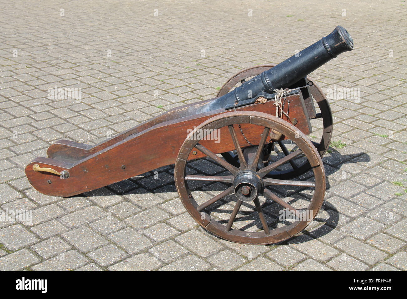 A Vintage Naval Cannon on Large Wooden Wheels. - Stock Image