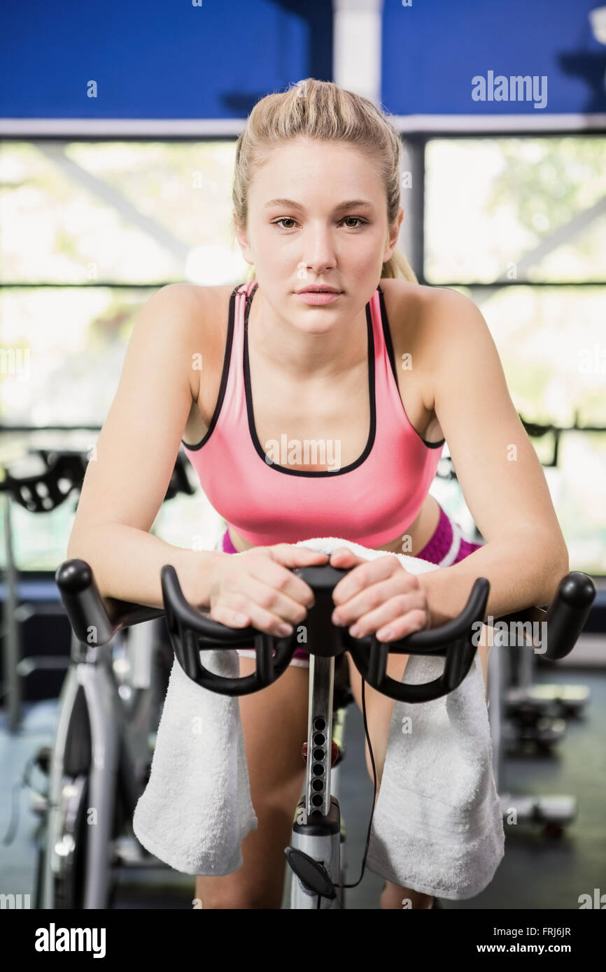 Woman sitting on exercise bike - Stock Image