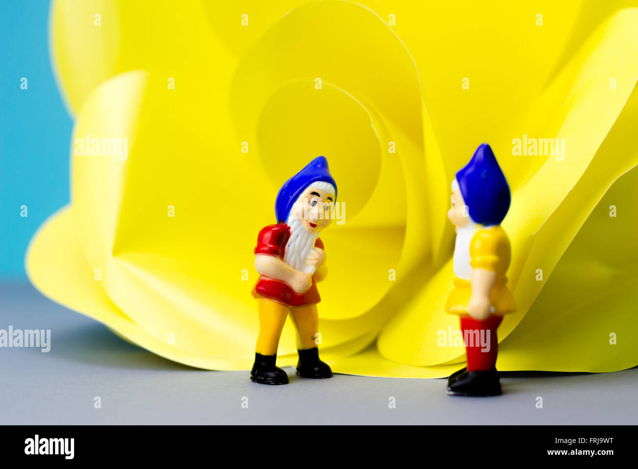 Miniature dwarves with giant flower on blue background Stock Photo