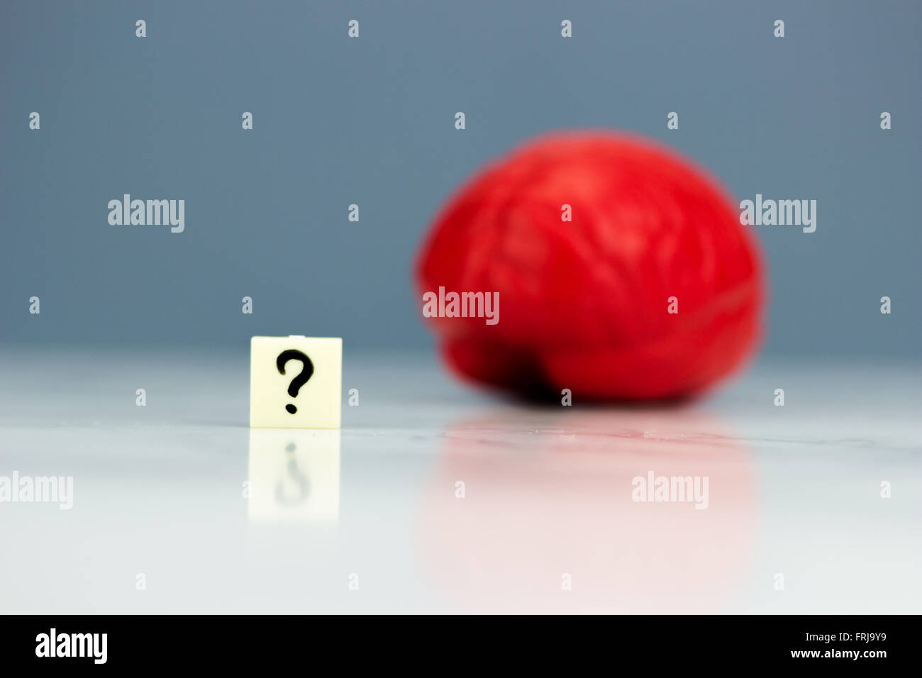 Red brain with question mark on dark background - Stock Image