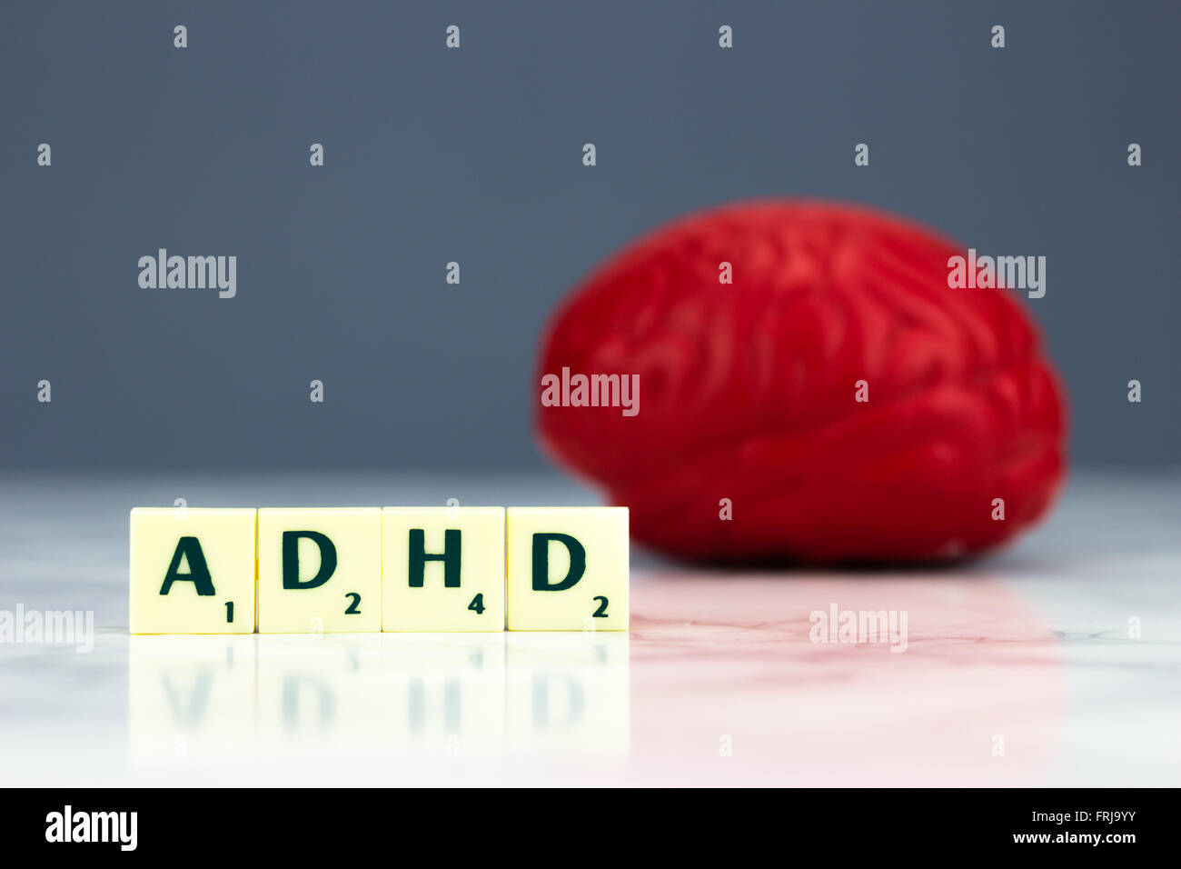 Red brain with ADHD sign on dark background - Stock Image
