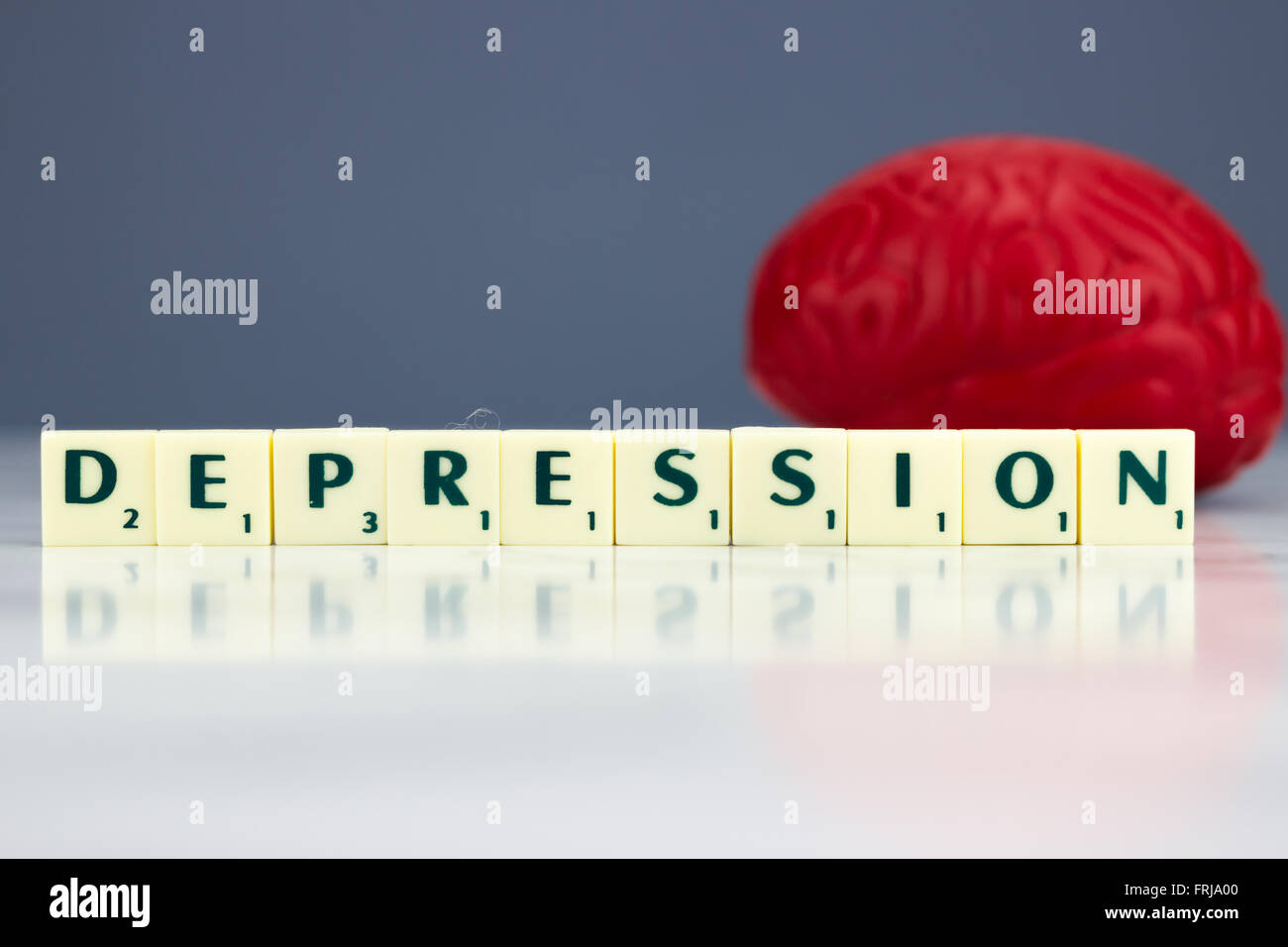 Red brain with depression sign on dark background - Stock Image