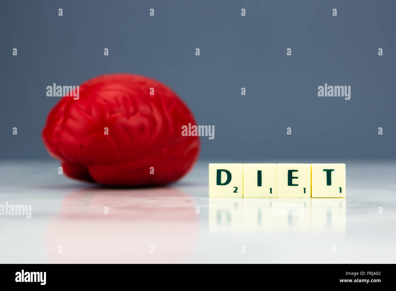 Red brain with diet sign on dark background - Stock Image