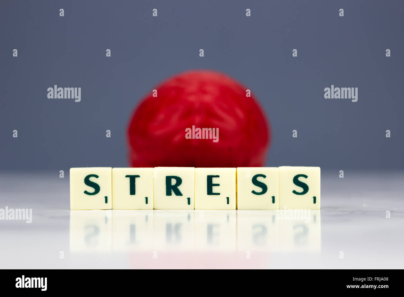Red brain with stress sign on dark background - Stock Image
