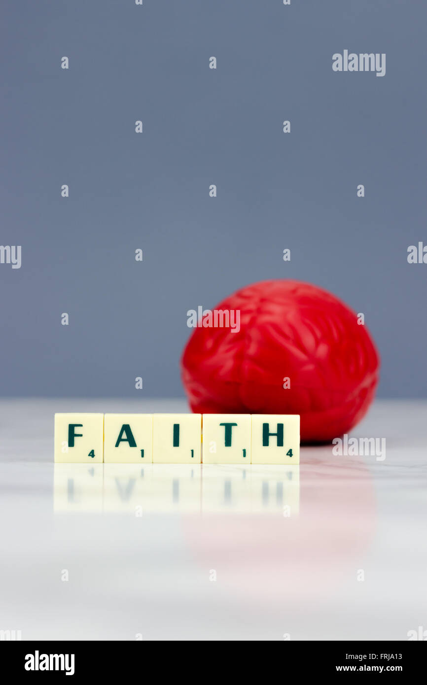 Red brain with faith sign on dark background - Stock Image