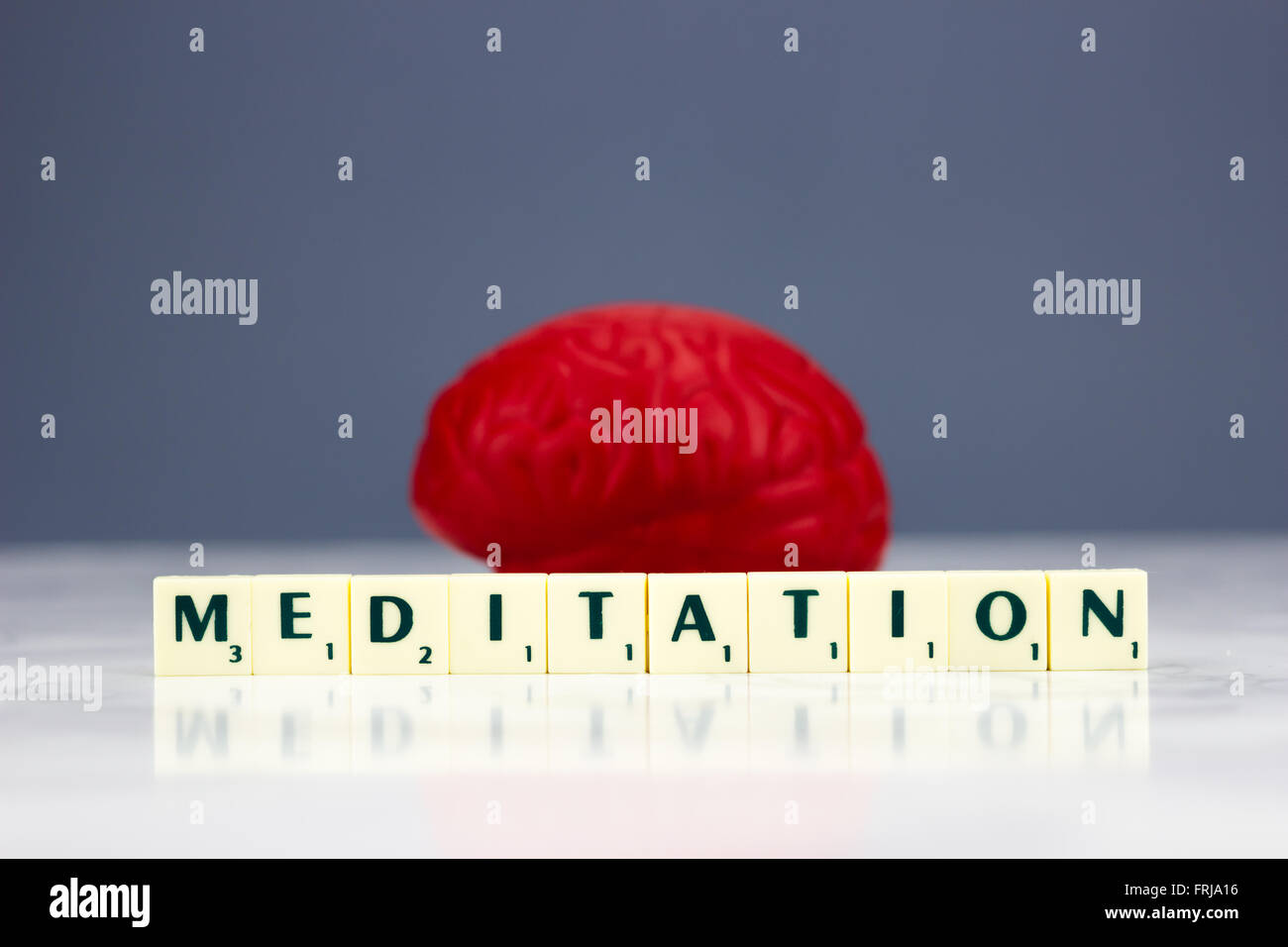 Red brain with meditation sign on dark background - Stock Image