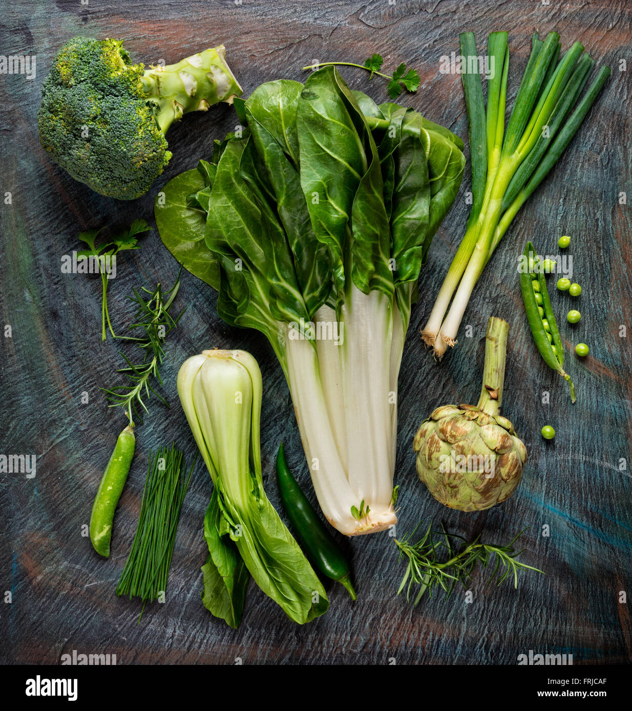 Collection of fresh green vegetables on black stone - Stock Image