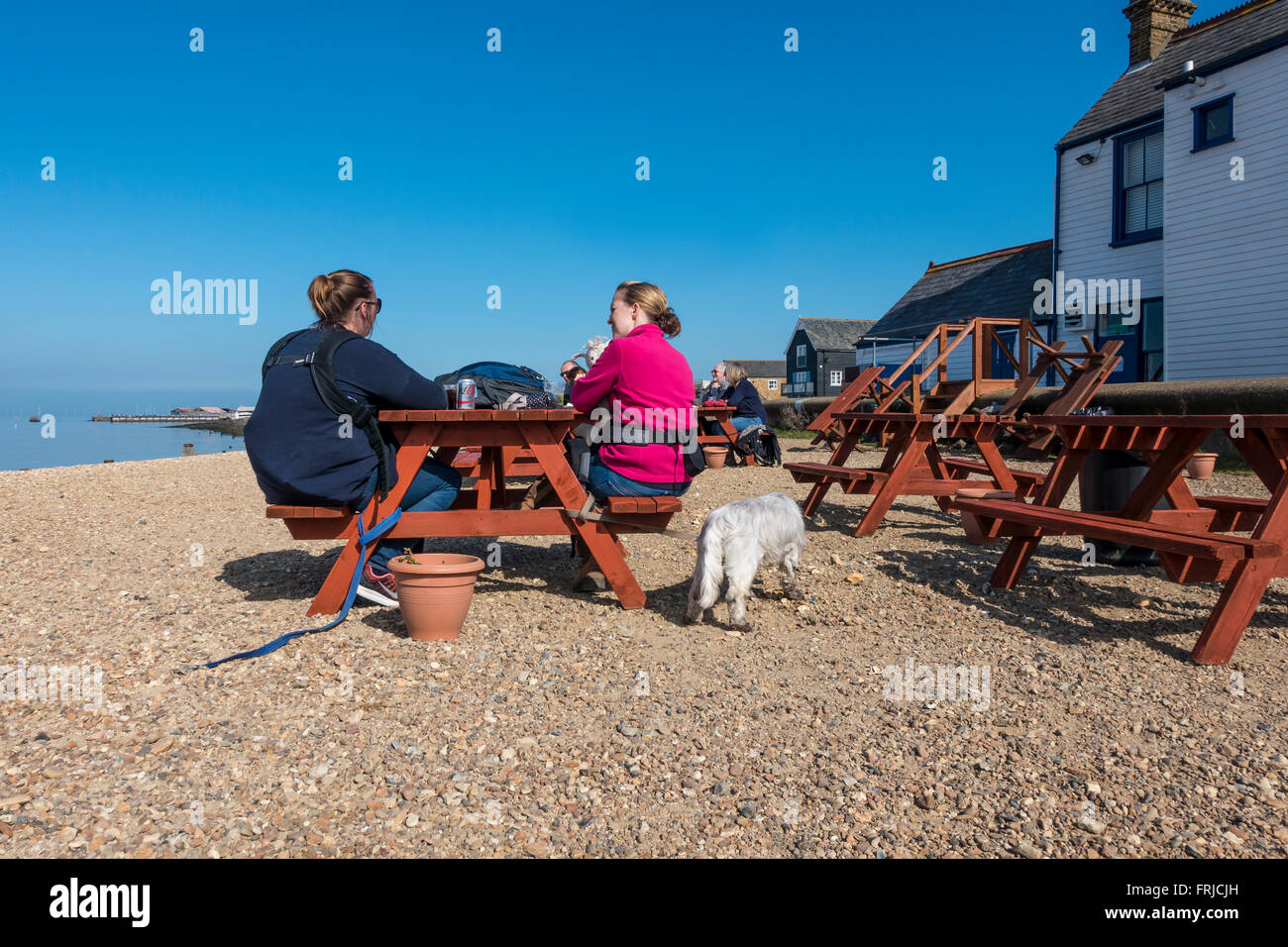 Two Women Chatting on Whitstable Beach Kent England - Stock Image
