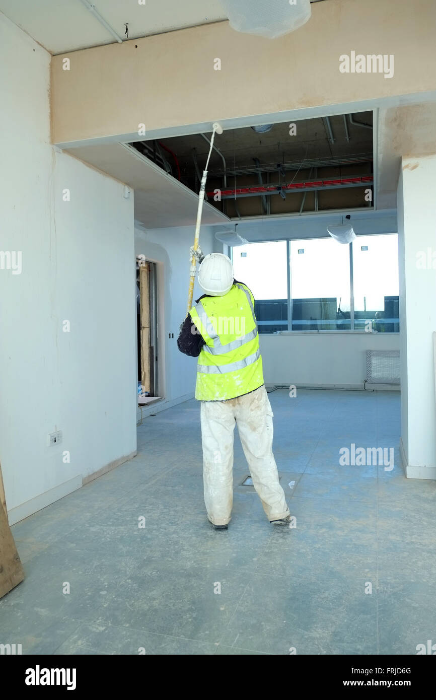 Commercial Decorator At Work Painting A High Ceiling With An Extended Paint  Roller