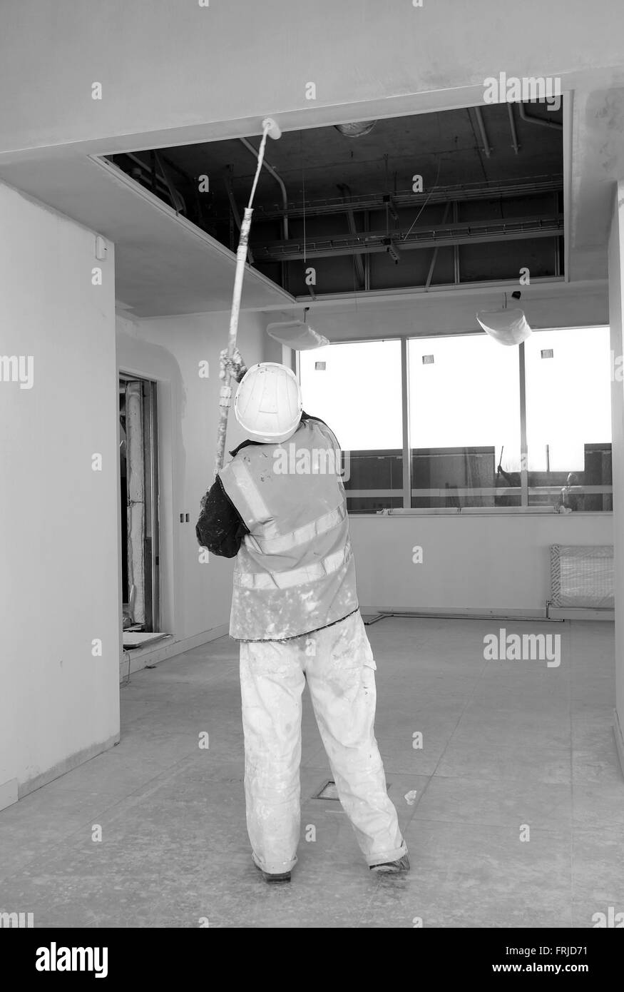 Commercial Decorator At Work Painting A High Ceiling With An